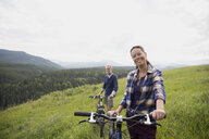 Portrait smiling senior couple with mountain bikes in remote rural field - HEROF13863