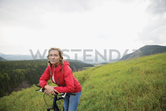 Portrait serious woman leaning on mountain bike in remote rural field - HEROF13866 - Hero Images/Westend61