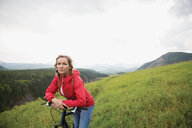 Portrait serious woman leaning on mountain bike in remote rural field - HEROF13866