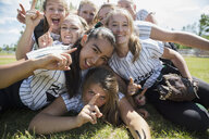 Portrait confident middle school girl softball team gesturing number 1 on field - HEROF13896