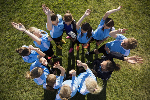 Overhead view middle school girl soccer team cheering in huddle with coach on field - HEROF13905