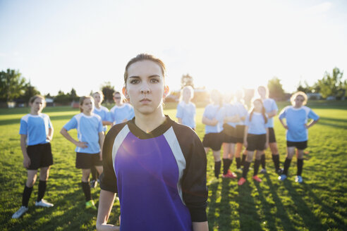 Portrait confident middle school girl soccer goalie showing attitude with teammates on sunny field - HEROF13911