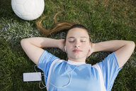 Overhead view serene middle school girl soccer player listening to music with headphones and mp3 player eyes closed - HEROF13917