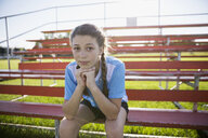 Portrait confident middle school girl soccer player on bleachers - HEROF13923