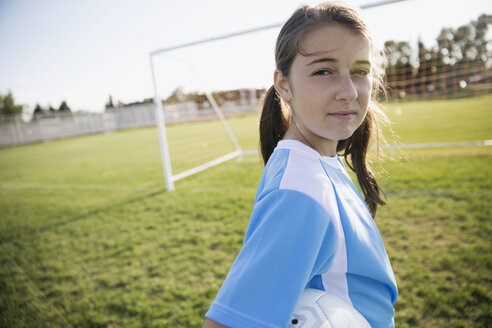 Portrait confident middle school girl soccer player showing attitude on sunny field - HEROF13926