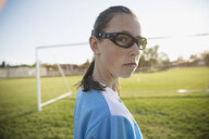 Portrait confident middle school girl soccer player wearing goggles on field - HEROF13929