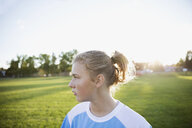 Pensive middle school girl soccer player looking away on sunny field - HEROF13932