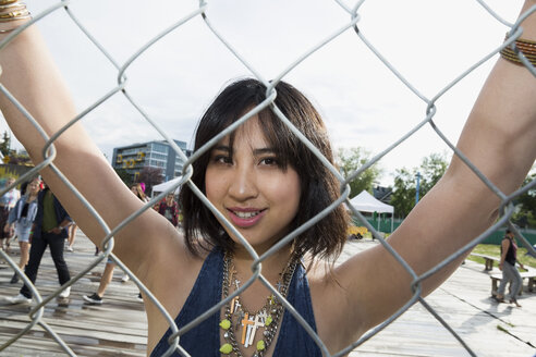 Portrait confident young brunette woman leaning on chainlink fence at summer music festival - HEROF13938