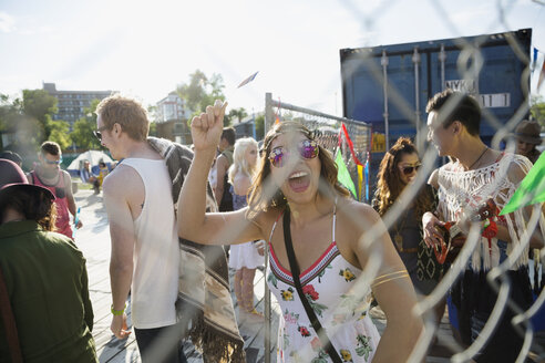 Portrait enthusiastic young woman waving summer music festival tickets inside gate - HEROF13947