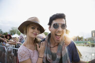 Portrait enthusiastic young couple at summer music festival - HEROF13965