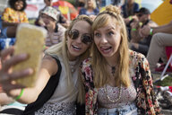 Playful young women making a face taking selfie at summer music festival campsite - HEROF13968