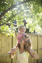 Playful mother carrying daughter on shoulders below apple tree in sunny backyard - HEROF13986