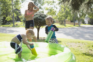 Playful brother and sister with squirt guns in wading pool in sunny yard - HEROF13989