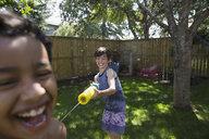 Playful boys using squirt gun in backyard - HEROF13995