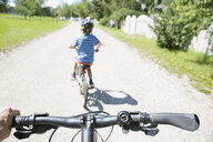Personal perspective following boy riding bicycles on sunny road - HEROF13998