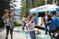 Playful friends dancing and drinking outside camper van at remote lakeside - HEROF14007