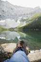 Personal perspective man in hiking boots relaxing with feet up on rocks at remote lake - HEROF14016