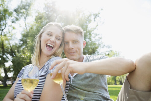 Portrait happy blonde couple drinking champagne in sunny summer park - HEROF14046