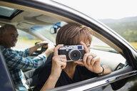 Portrait mature woman using camera in car window - HEROF14049