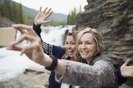 Playful women friends waving taking selfie with camera phone near waterfall - HEROF14058