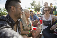 Young friends drinking and hanging out at summer music festival - HEROF14067