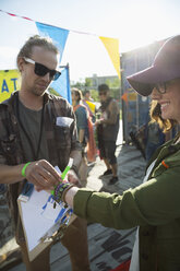 Young woman receiving wristband at summer music festival entrance - HEROF14079