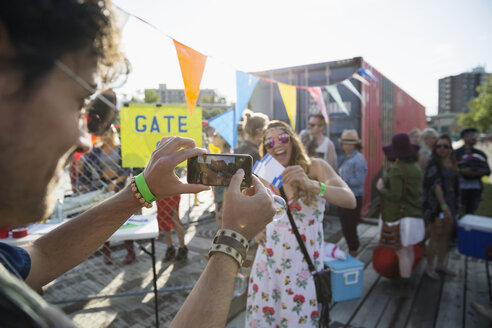 Young woman with summer music festival tickets posing for photograph outside entrance - HEROF14082