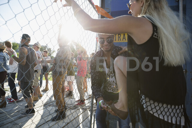 Young man helping woman climb fence at summer music festival - HEROF14088 - Hero Images/Westend61