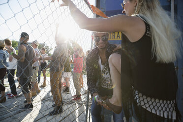 Young man helping woman climb fence at summer music festival - HEROF14088