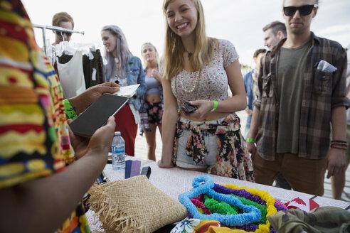 Young woman using credit card reader at vendor booth at summer music festival - HEROF14100