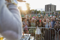 Young crowd cheering DJ on stage at summer music festival - HEROF14115