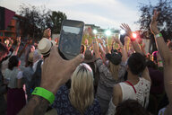 Young man in crowd taking video with smart phone at summer music festival - HEROF14118