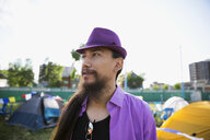 Young man with long hair and beard wearing purple hat looking away at summer music festival campsite - HEROF14121