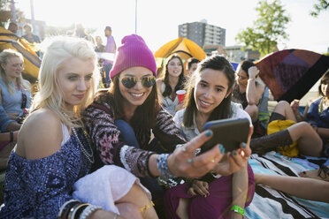 Young women taking selfie at summer music festival campsite - HEROF14124