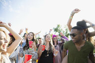 Young crowd drinking and dancing at summer music festival - HEROF14133