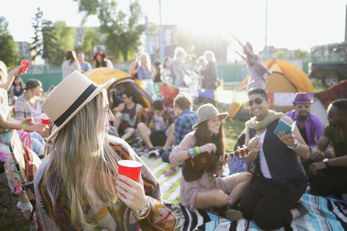 Young friends hanging out and drinking at summer music festival campsite - HEROF14136