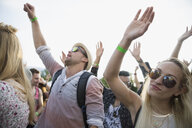 Young crowd cheering and dancing at summer music festival - HEROF14139