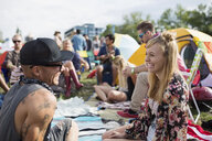 Young couple hanging out with friends at summer music festival campsite - HEROF14148