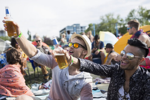 Young men drinking beer cheering at summer music festival campsite - HEROF14151
