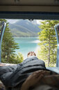 Woman laying in back of camper van with remote lake view - HEROF14190