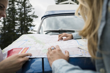 Women viewing map on camper van - HEROF14196
