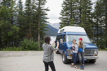Woman with camera phone photographing friends outside camper van at lakeside - HEROF14199