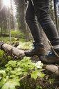 Woman in hiking boots walking along fallen tree in woods - HEROF14205