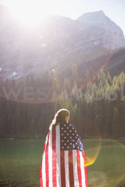 Woman wrapped in American flag enjoying sunny remote mountain lake view - HEROF14211