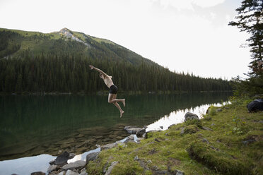 Young man in swim trunks jumping into remote lake - HEROF14214