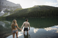 Young couple holding hands wading into remote lake - HEROF14217