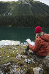 Woman writing in journal at remote lakeside - HEROF14220