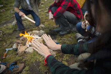 Woman warming hands over campfire - HEROF14226