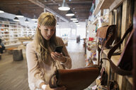 Woman shopping photographing leather handbag with camera phone in shop - HEROF14232