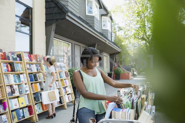 Woman browsing books at bookstore storefront sidewalk bin - HEROF14244 - Hero Images/Westend61